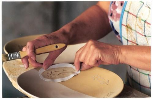 Trabajo artesanal de decoración cerámica sobre un plato en la Bisbal d'Empordà