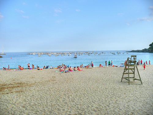 Arena dorada en la playa de Llafranc. Al fondo, el puerto deportivo.