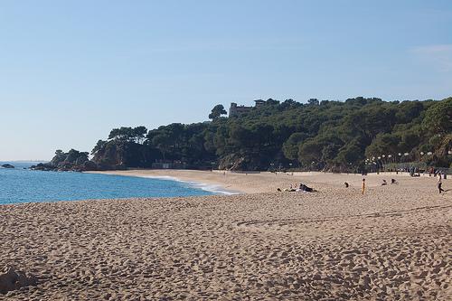 La playa de Fenals ofrece un extenso arenal. Vista hacia el sur.