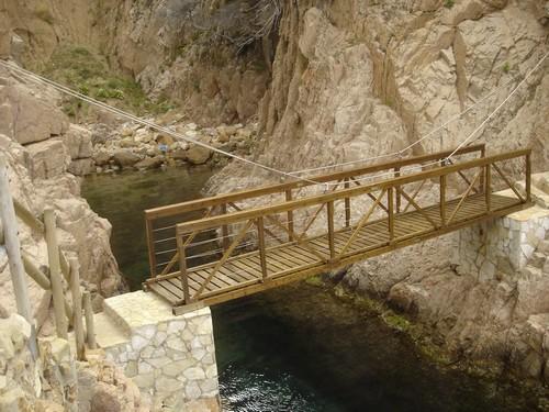 Pequeño aunque moderno puente de madera que cruza el camino de ronda de Cala Salionç