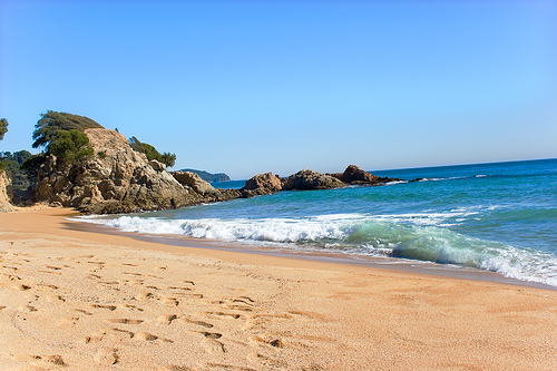 A través de las rocas que surgen de la arena, a la izquierda de la cala, podemos alcanzar la Cala de Santa Cristina
