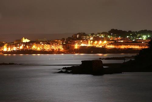 Idílica imagen nocturna de la Playa Moll Grec, con el perfil del muelle y, al fondo, l'Escala