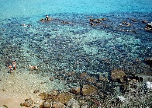 Las aguas transparentes de la playa de la Fosca contrastan con sus rocas negras