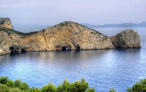 La Roca Foradada, gran roca con túnel navegable, se encuentra cerca de Cala Ferriol, en l'Escala