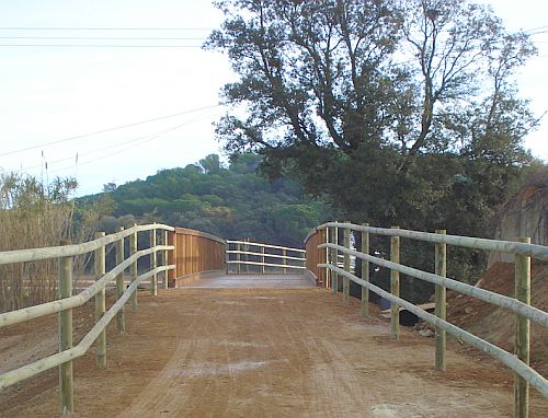 Este puente de madera tan bien construido sobre la vía verde del Tren Petit permite atravesar la riera d'Aubi