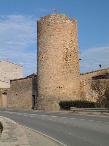 Se puede apreciar, a la derecha de la imagen, como una pequeña puerta en forma de arco da acceso al jardín que se encuentra junto a la Torre de les Bruixes, en Torroella de Montgrí