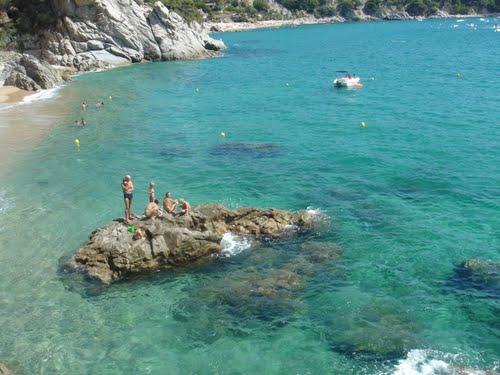 A los bañistas les encanta encaramarse sobre las rocas situadas frente a la playa Porto Pi para obtener las mejores vistas de la bahía de Llorell, entre Tossa de Mar y Lloret de Mar, en la Costa Brava