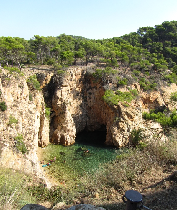 Justo frente a la Cala de Sa Corbatera se encuentra la roca Foradada, que se puede cruzar tanto a nado como en canoa. Palamós, Girona, Costa Brava