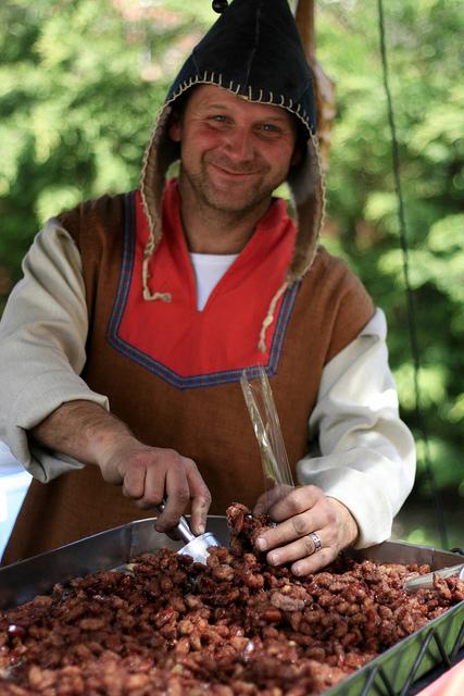 El vendedor de almendras garrapiñadas de la Feria Medieval de Calonge, en la Costa Brava, nos sonríe mientras nos las sirve, vestido de época