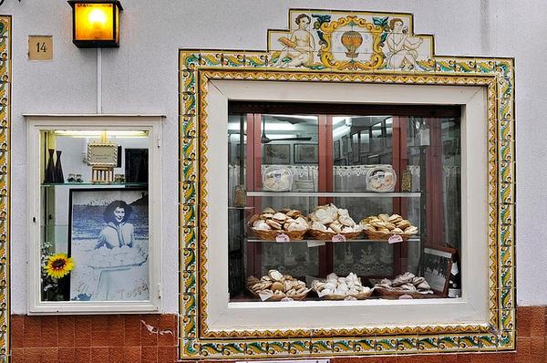Paseando por Tossa de Mar encontramos en el escaparate de una pastelería esta foto de época de Ava Gardner, sosteniendo una bandeja con los postres tradicionales de la localidad