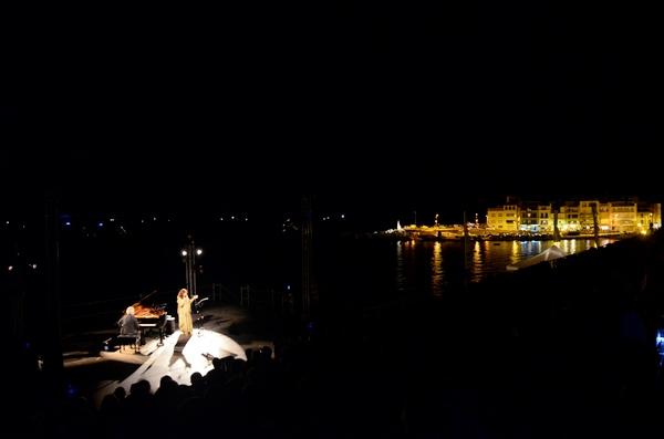 Las playas de l'Escala, con el centro del pueblo iluminado al fondo, también se convierten en escenarios donde la música se mezcla con la brisa marina