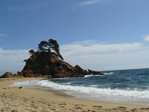 Playa Sant Jordi-Cap Roig, a pesar de su espectacular roca, ofrece una buena extensión de arena para que el bañista pueda relajarse tumbado en la arena