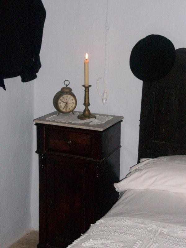En el piso de arriba de Can Cinto Xuà, por donde continúa la visita guiada, se encuentran los dormitorios. Junto a la cama podemos observar una vela y un despertador de época.