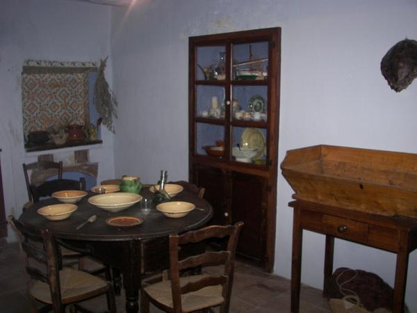 La mesa del salón de la Casa de Pescadores Can Cinto Xuà parece encontrarse preparada para la comida. De esta manera podemos observar el menaje que utilizaban por entonces.