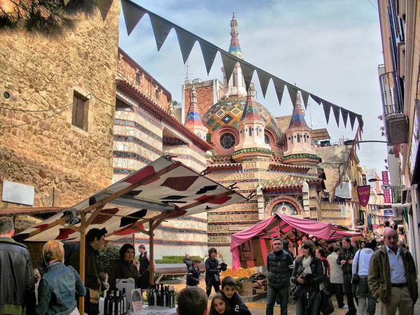 Las familias se pasean tranquilamente por los diferentes y variados puestos del Mercado Medieval de Lloret de Mar, y justo enfrente de la original iglesia de Sant Romà.
