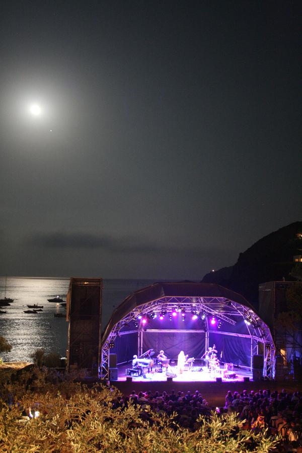 Algunos de los conciertos del Festival Internacional de Música de Cadaqués tienen lugar en el Oliverar de Sa Conca, un jardín de olivos que se encuentra frente a la playa del mismo nombre. El faro que se ve sobre la pendiente de la montaña, sobre el escenario, es el de Cala Nans