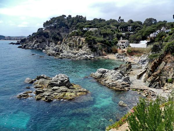 Caleta d'en Trons, en Lloret de Mar, es una cala de gran belleza paisagística, rodeada de rocas, pero que también cuenta con una superficie de arena ideal para los bañistas que la frecuentan