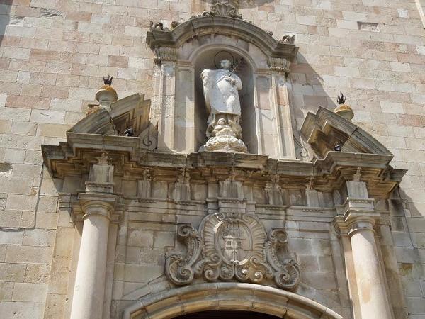 La puerta de entrada a la iglesia de San Vicente de Tossa de Mar muestra sobre el arco, y dentro de una hornacina vertical, la estatua del santo venerado aquí