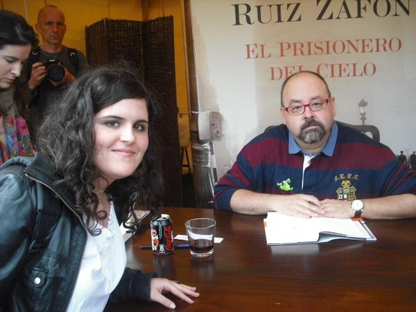 Durante la Diada de Sant Jordi los principales autores también se encuentran en las paradas del mercado para dedicar sus libros a los lectores, que aprovechan a su vez la ocasión para retratarse con ellos. Aquí tenemos al escritor Carlos Ruiz Zafón.