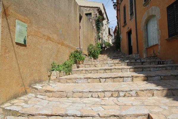 Las escaleras que suben hasta el Castillo de Begur también forman parte de la ruta literaria Joan Vinyoli. Atención al cartel de la izquierda, sobre la pared. Iremos encontramos los respectivos paneles en cada punto de la ruta con la información contextual ilustrada del punto de interés.