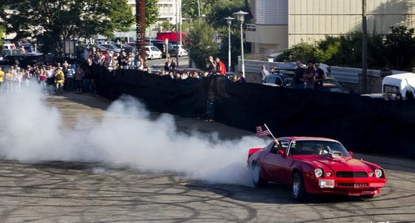 Uno de los vehículos de exhibición del Encuentro de Coches Americanos de Platja d'Aro en plena acción, quemando rueda sobre el asfalto para goce de los asistentes