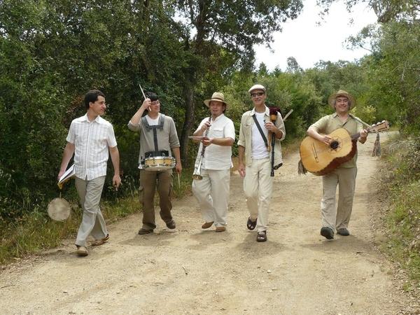 Un grupo de músicos se dirige al bosque de las Gavarres de Llofriu para formar parte de la ceremonia de la Pela del Corcho. Más tarde volverán al centro del pueblo y continuarán animando las calles durante la feria, mercado artesanal y los talleres infantiles