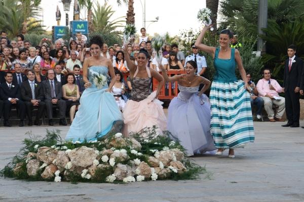 Las jóvenes estrellan la 'almorratxa' contra una gran piedra en el centro de la Plaza del Ayuntamiento en Lloret de Mar: es el Ball de Plaça, en el marco de las Fiestas de Santa Cristina, el 24 de julio en Lloret de Mar