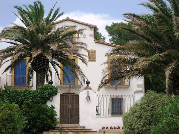 La fachada del Museo de la Magia de Santa Cristina es típica de la antigua masía decimonónica que es. Frente a ellas dos preciosas palmeras.