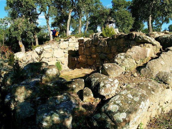 Dos visitantes pasean junto a los restos de una antigua casa ibérica de unos 23 siglos de antigüedad. El lugar es muy tranquilo e invita a reflexionar sobre la historia y la vida.