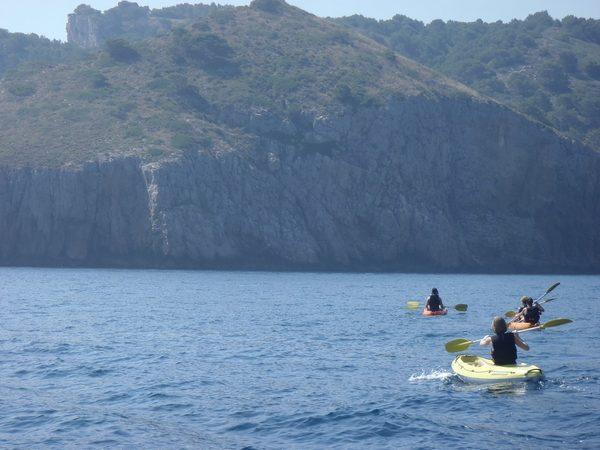 Un grupo de kayakistas se dirige hasta la Cova de la Sal, bajo el gran cabo de la Punta del Milà, entre Torroella de Montgrí i l'Escala, en pleno Parque Natural del Montgrí