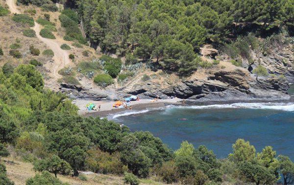 Imagen de Cala Calitjàs en pleno verano. Vemos también unas escaleritas de piedra que descienden desde el camino de ronda.